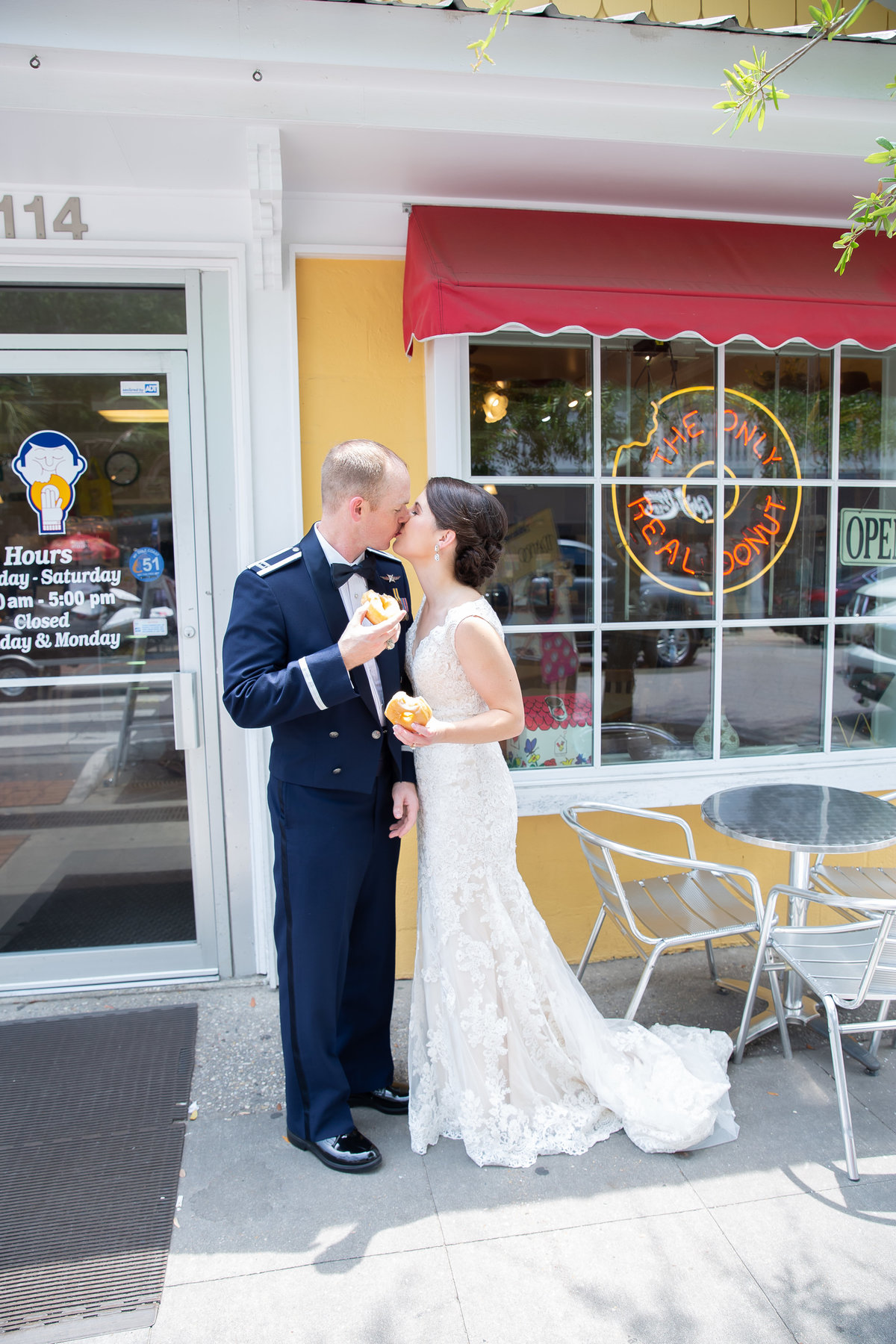 Bride and Groom with doughnut in front of Tatonut in dowtown Ocean Springs