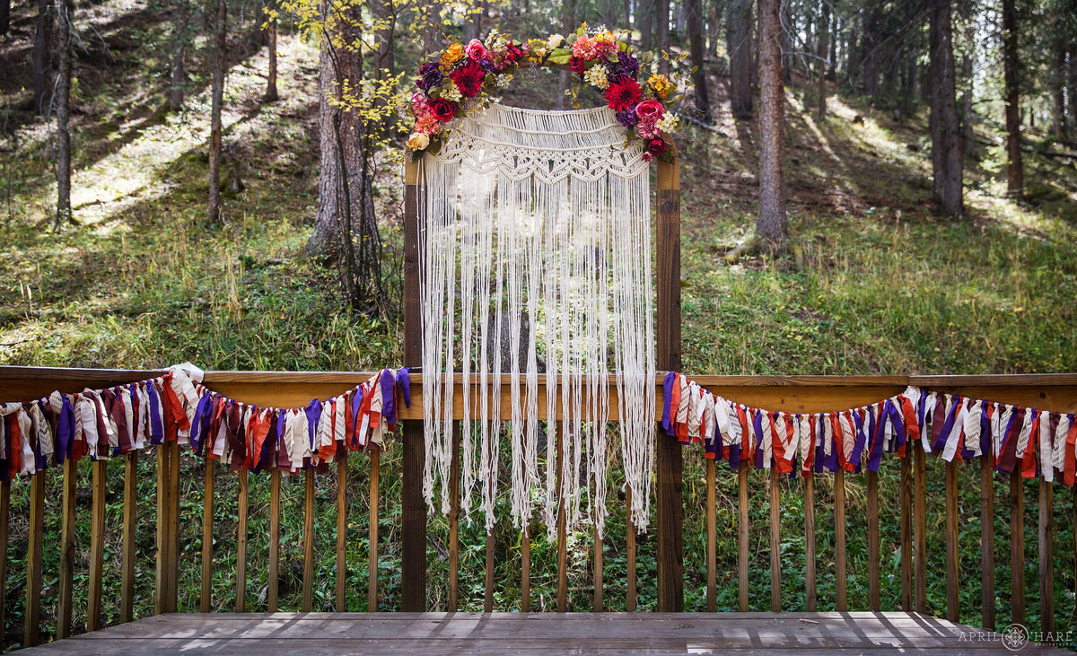 Pretty outdoor mountain wedding with custom Macrame backdrop at Beaver Meadows in Conifer CO