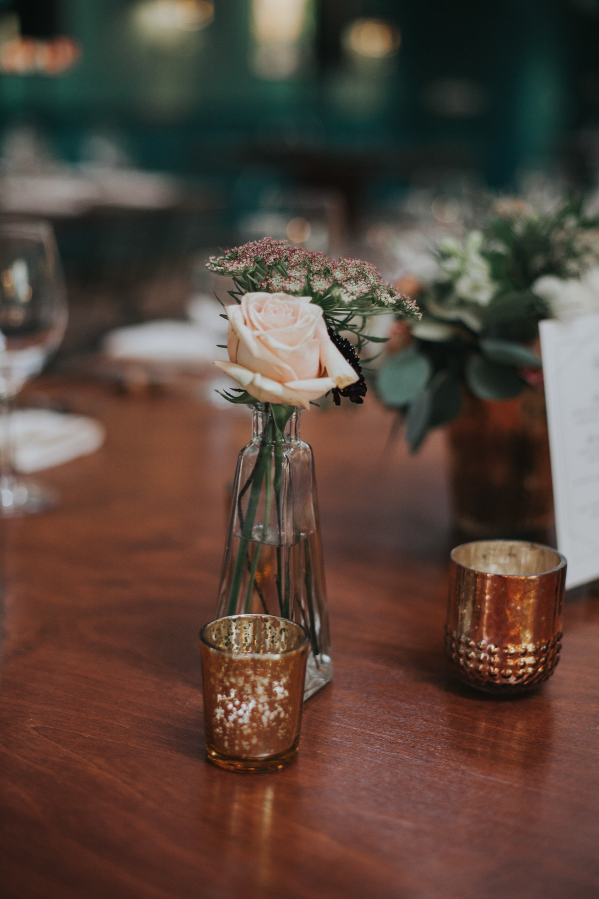 Wedding reception table setting with glass bud vase centerpiece at The Fig House