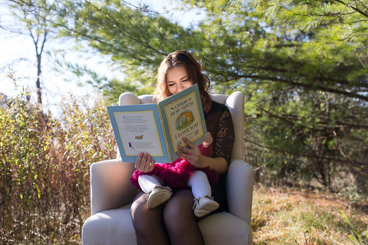 mother reading book to baby daughter in field {Burlington Family Photographer}