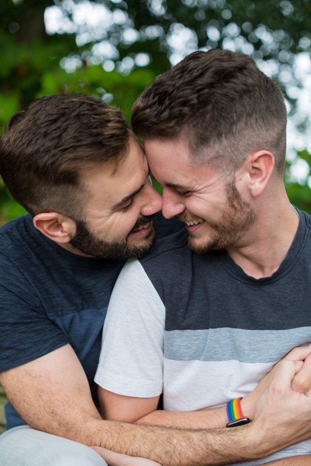 gay couple hugs for engagement portrait in Piedmont Park by Mike Glatzer Photography
