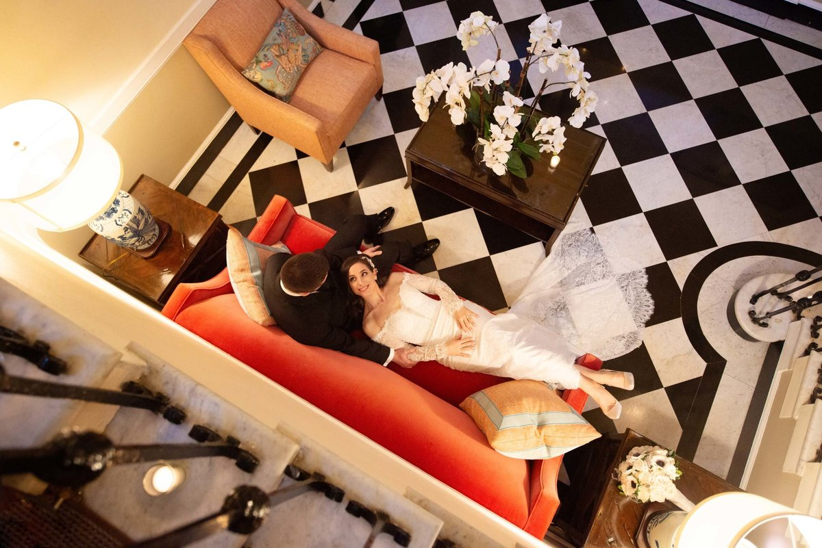 Bride and groom laying on the sofa at The Mansion at Oyster Bay