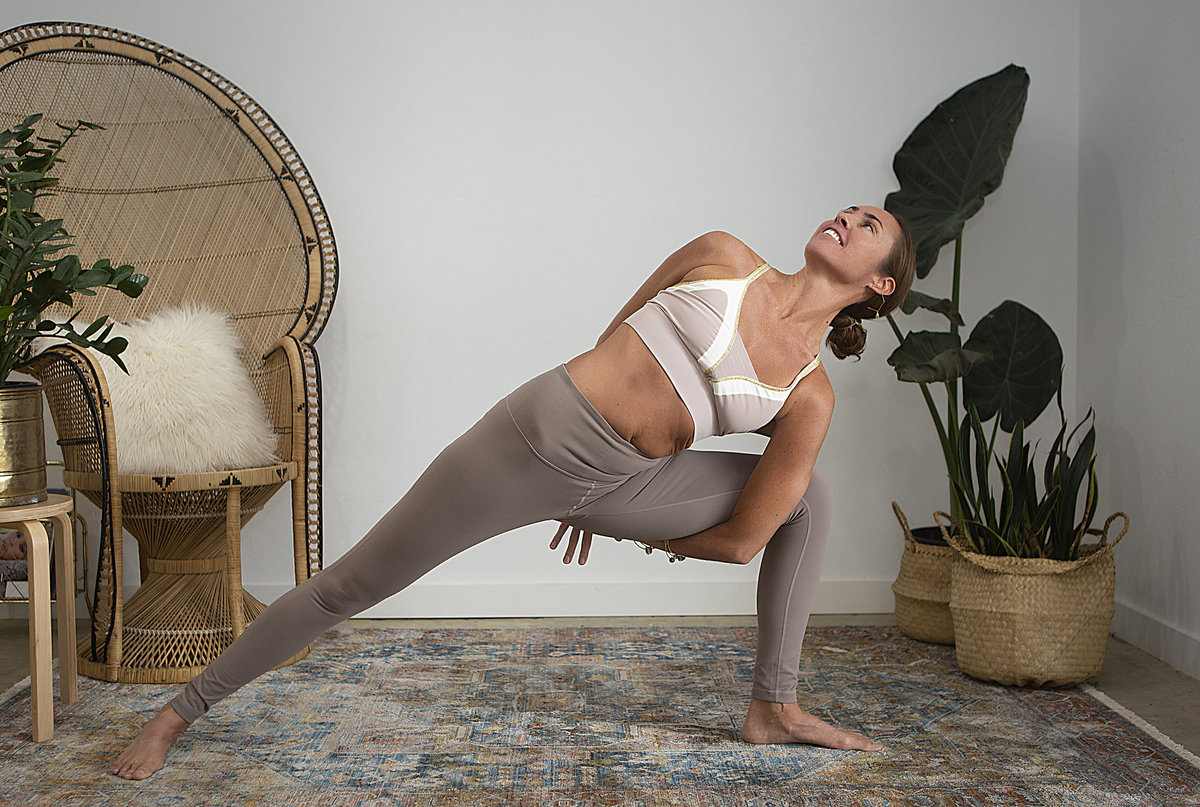 Female yogi holds bound crescent lunge twist yoga pose & smiles during yoga class at Hotsource Yoga in Aptos