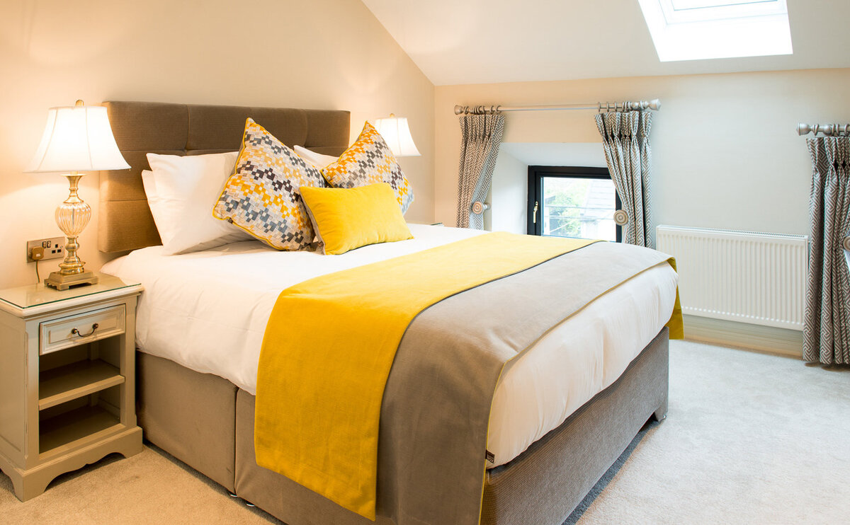 Hotel bedroom with double bed covered in yellow and grey bed linen