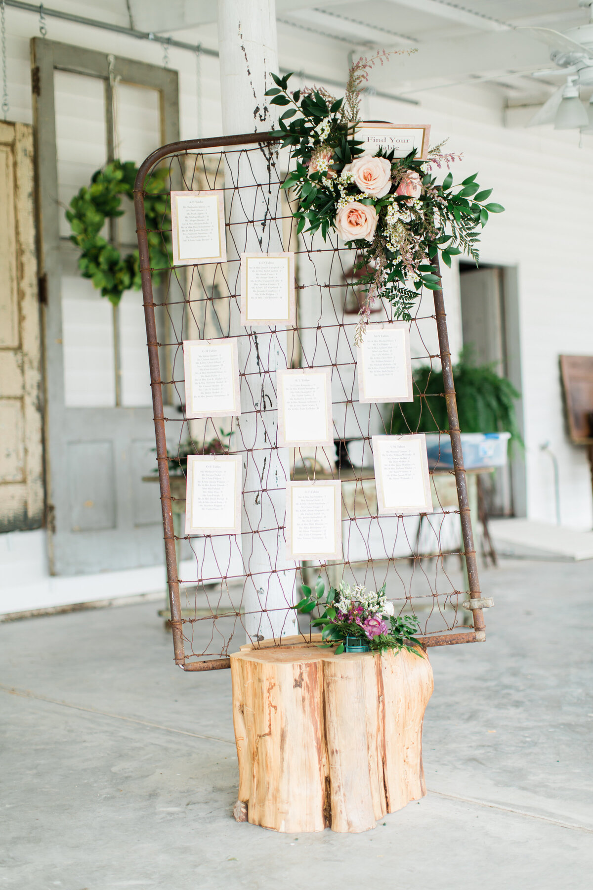 A stunning seating chart arrangement for a wedding. Displayed on a rustic vintage wire fence with florals hanging from it