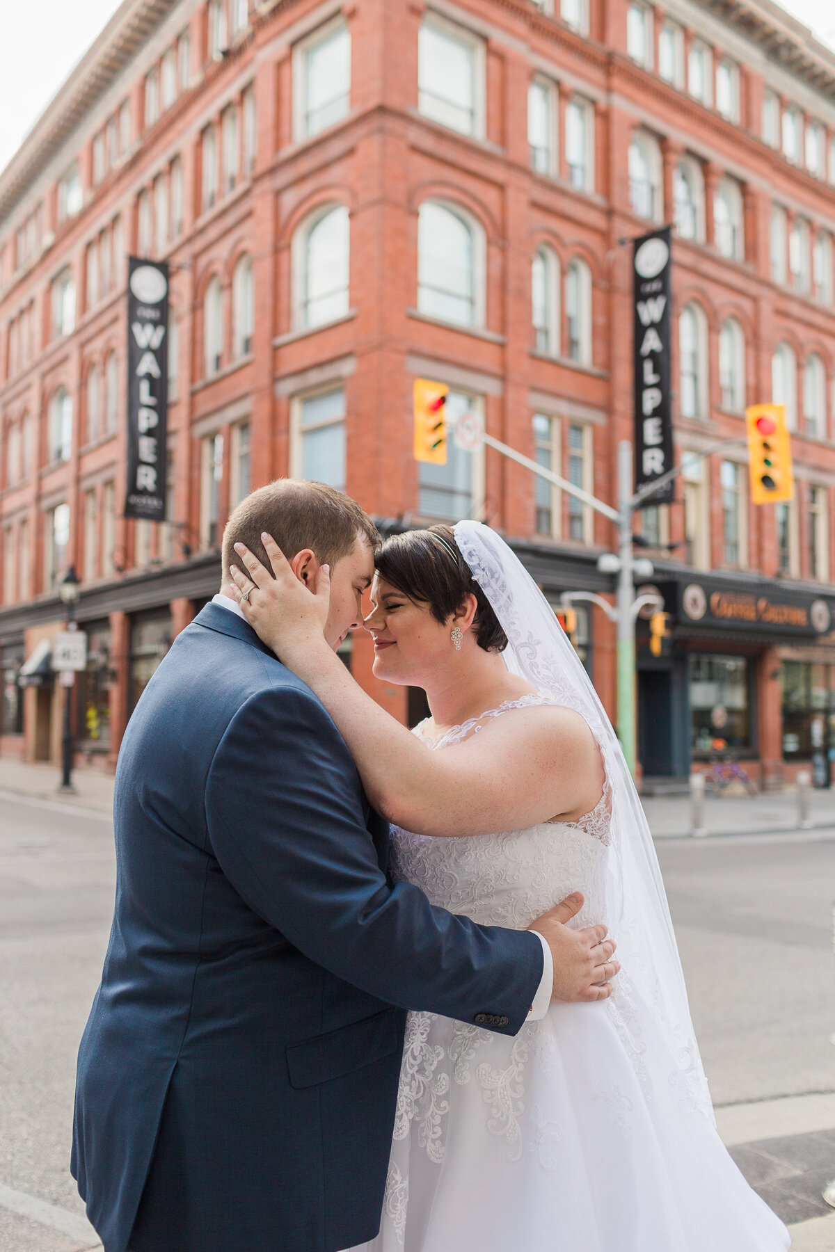 bride and groom kissing on a street corner