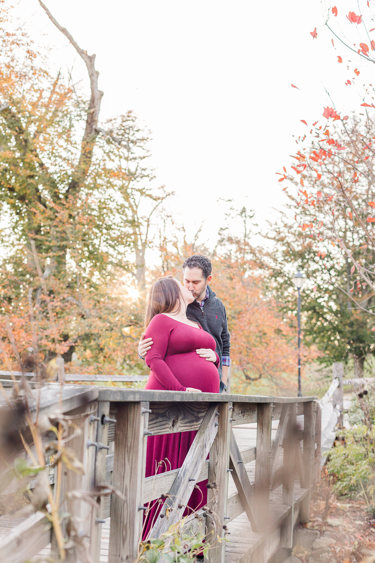 Maternity photo kiss on bridge Hunnewell park Wellesley MA