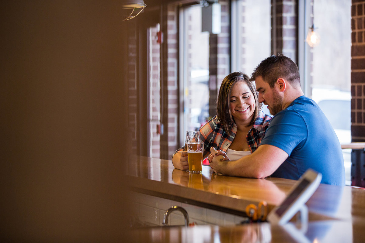 couple sharing a beer during their engagement session at a brewery