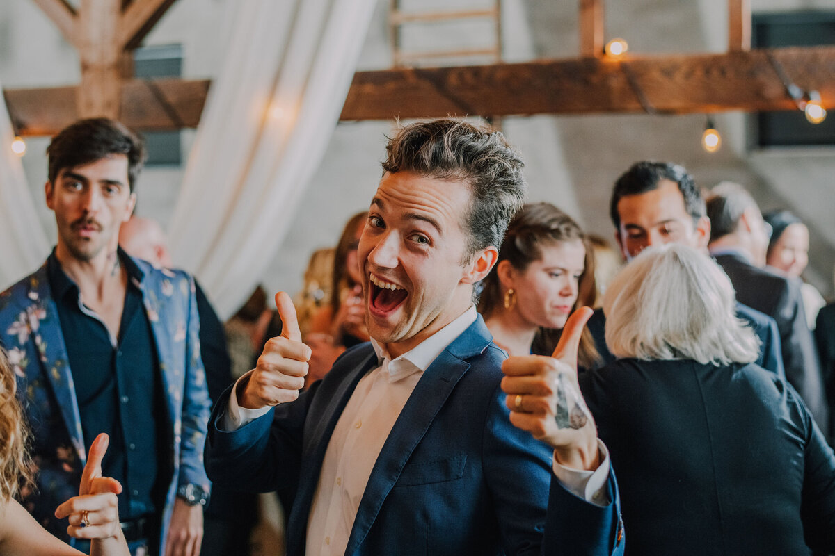 wedding guest wearing blue blazer gives both thumbs up at wedding reception in a barn at durham hill farm shot by wedding photographer in philadelphia alex medvick
