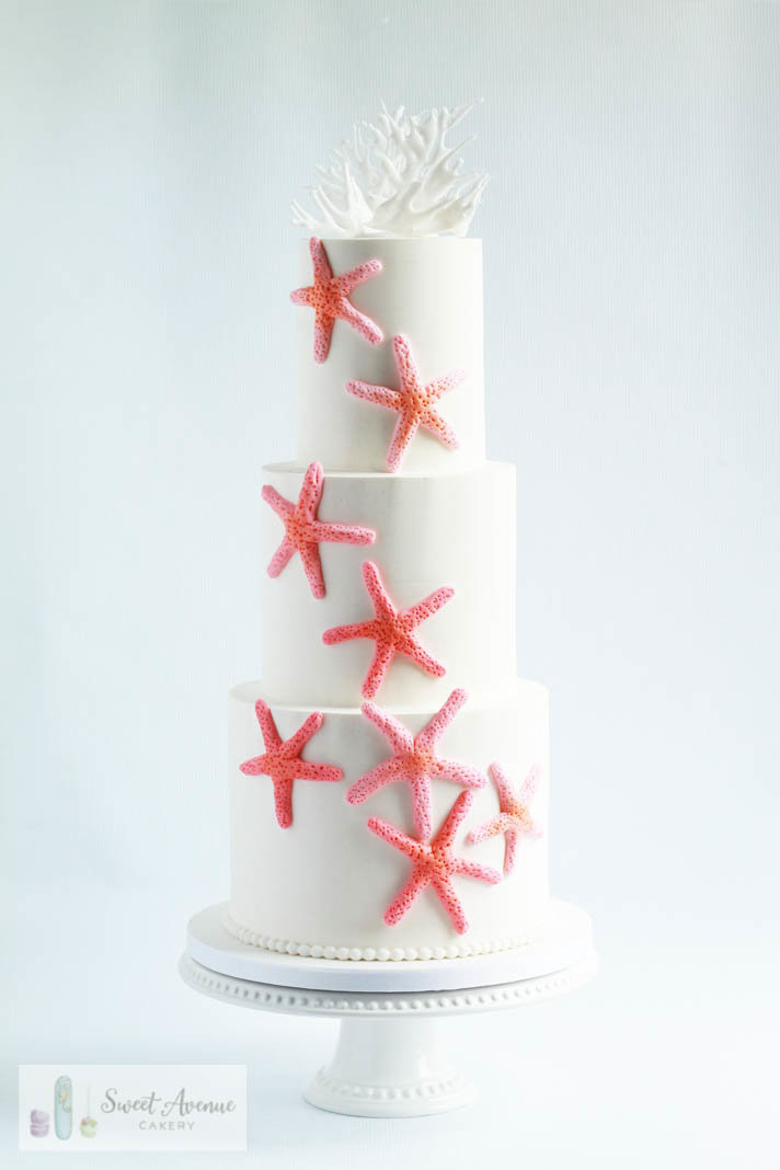 white wedding cake with peach sugar starfish and coral topper