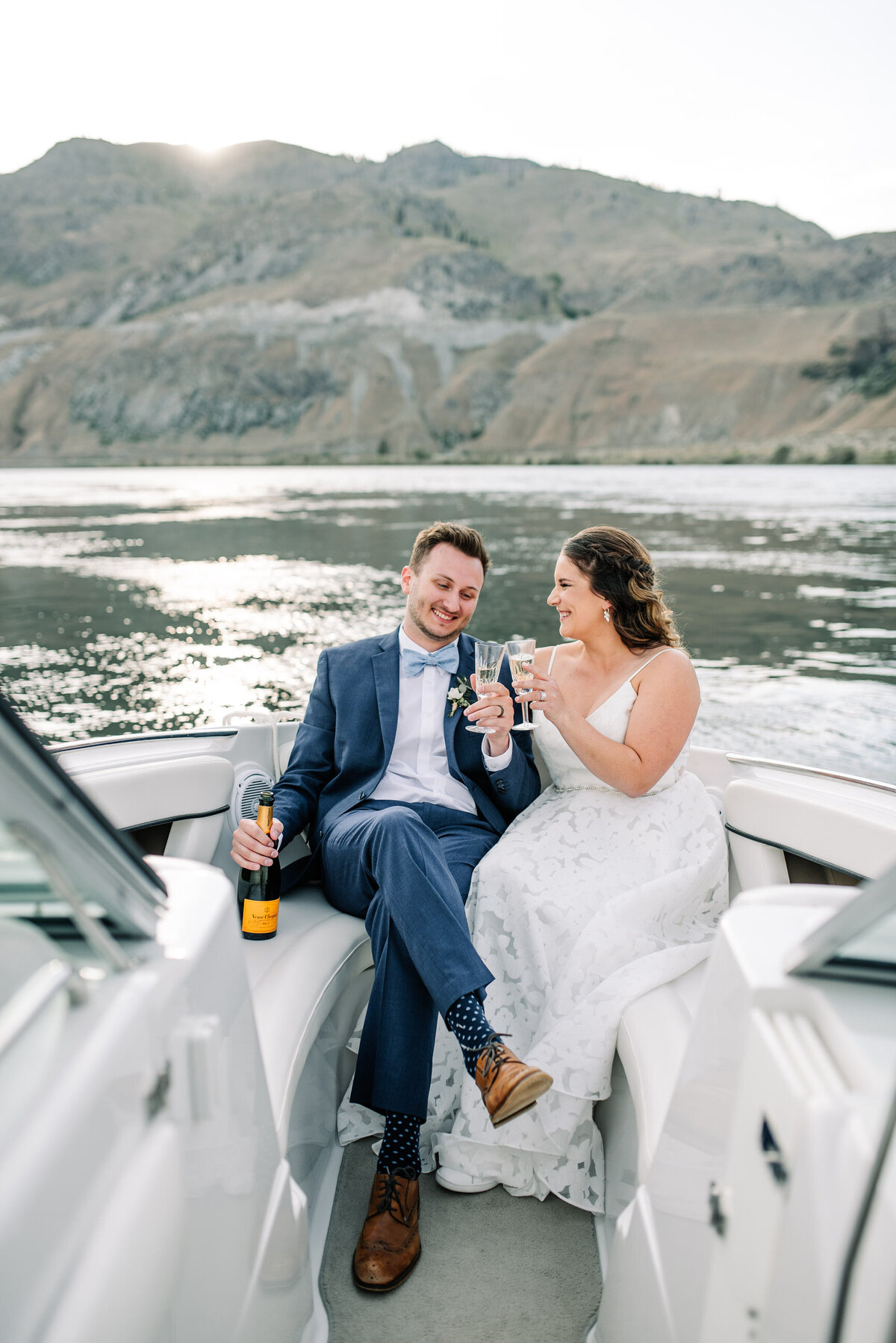 Bride and groom toast with champagne on a sunset boat ride on Lake Chelan
