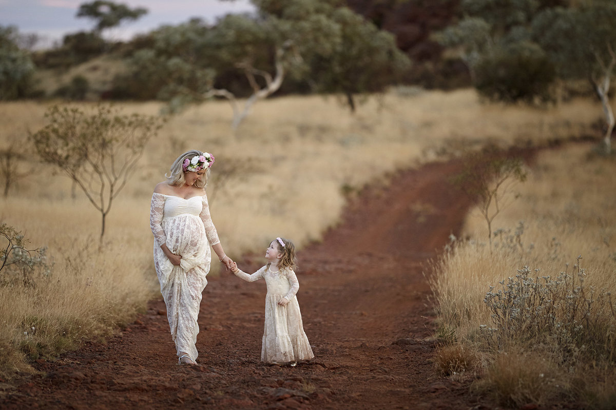 Pregnant mum holding daughters hand walking down a red dirt path looking at each other in matching white outfits