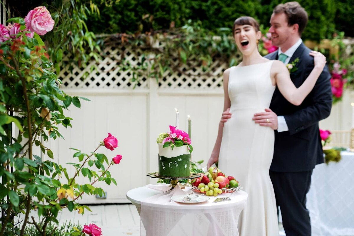 a bride laughs hard and leans on the groom in front of a pretty green and white wedding cake and table of fruit