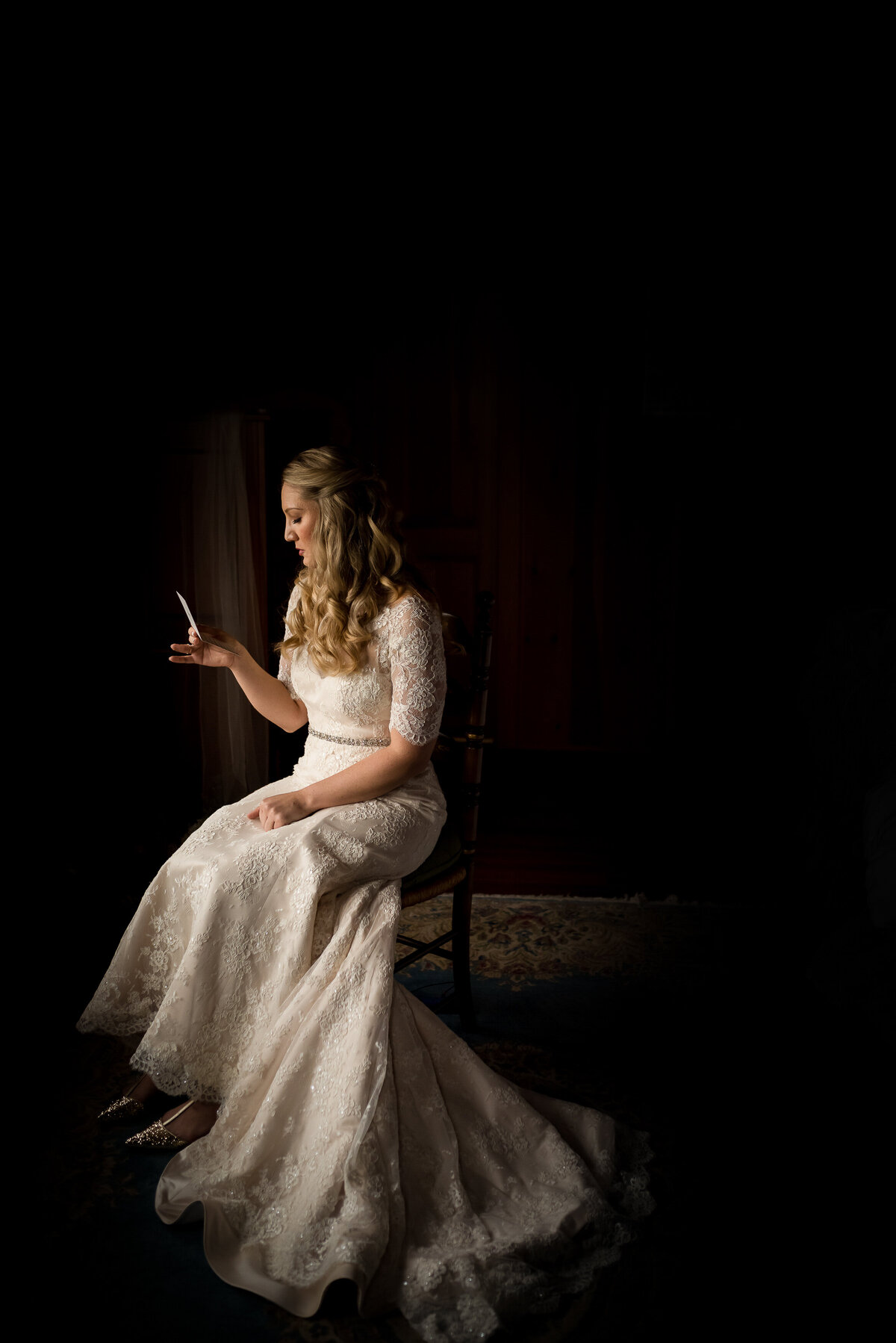 bride reading a letter from her groom before wedding ceremony