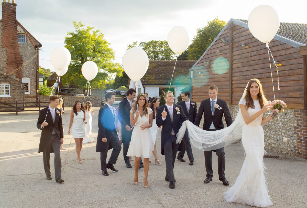 Bride and the entire bridal party with balloons and sunflare stolling away to have photos at Pangdean Barn wedding venue in East Sussex