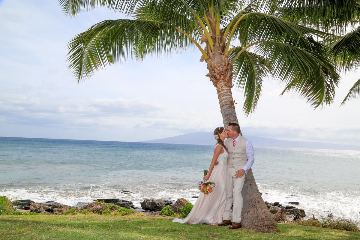 Capture Aloha Photography at The Westin Maui Resort and Spa With Kissing Bride and Groom at beach and coconut tree