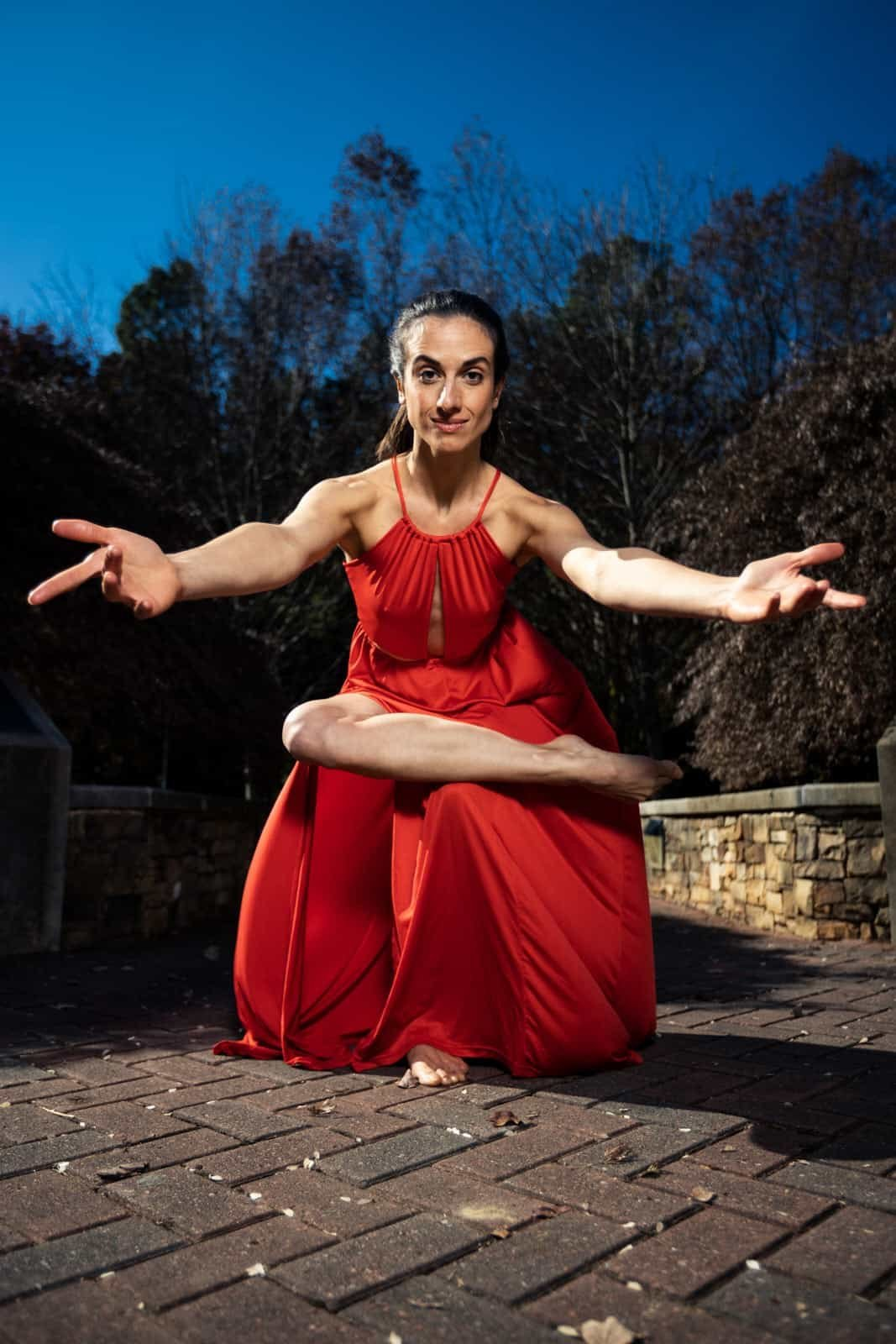 female ballet dancer in red dress dancing in stone courtyarrdr