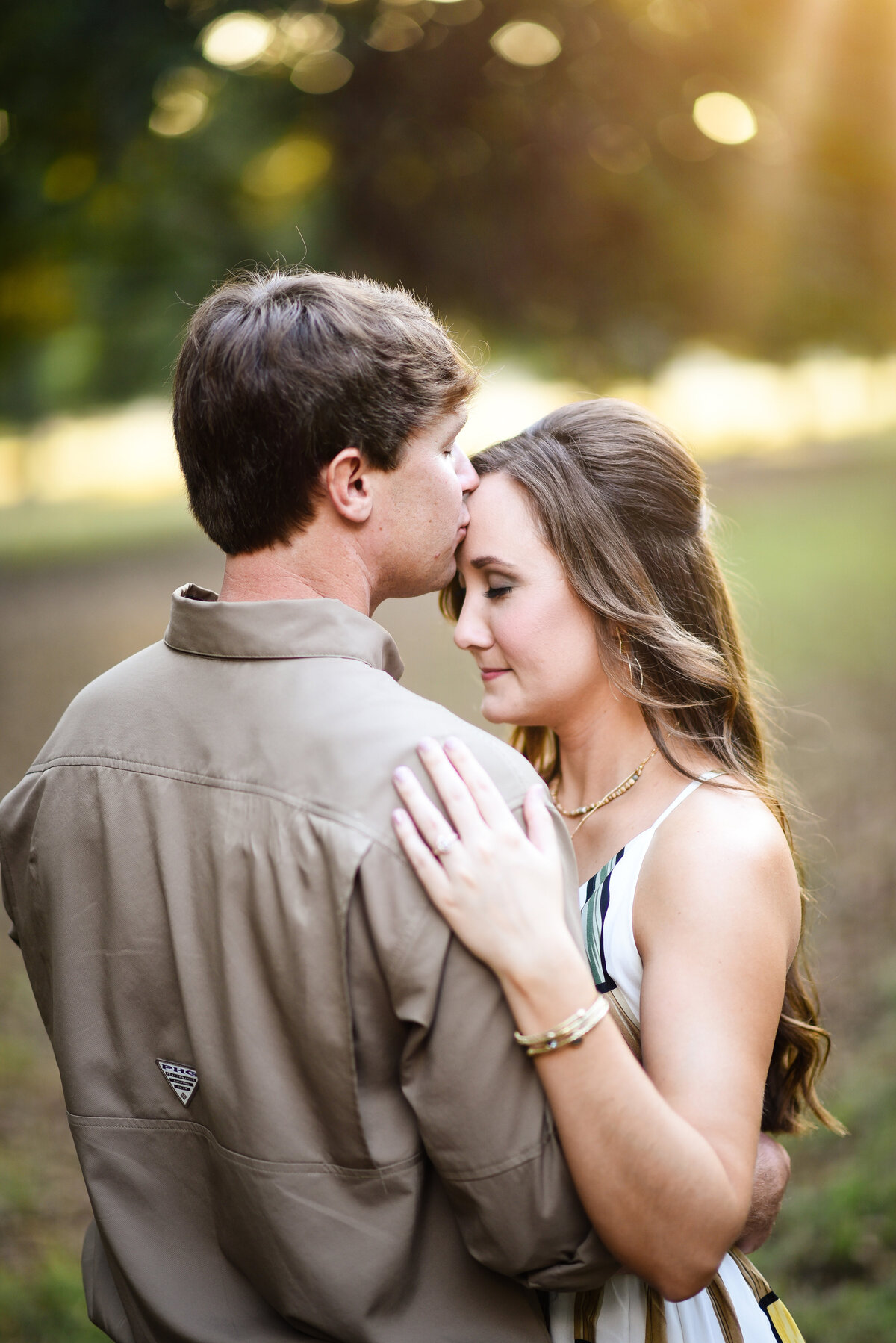 Beautiful Mississippi Engagement Photography: man kisses woman during golden hour sunset in Mississippi Delta Pecan Orchard