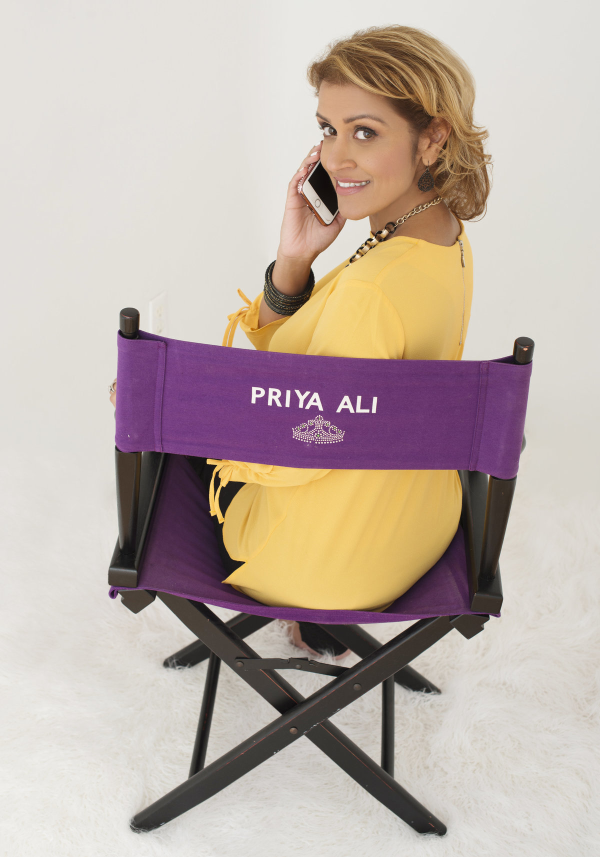 business brand photography of  film  director sitting on her chair talking on her phone and  smiling  photo