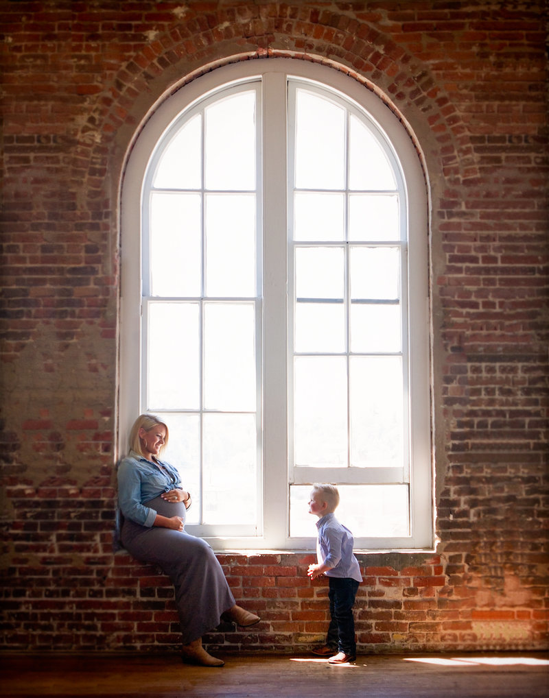 Sky 9 Studio | Professional family maternity photo of mother and son in front of large round top window against a brick wall.  Mother is pregnant and her son is lovingly looking up at her