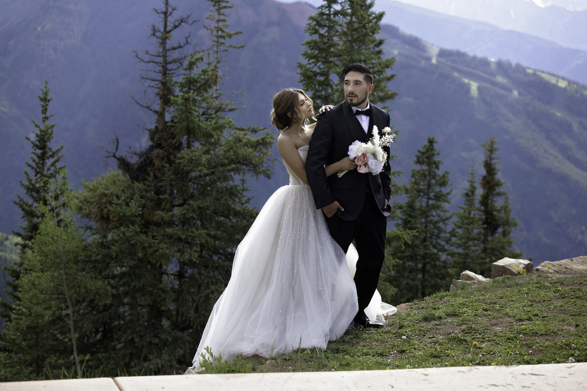 Bride and groom stand on a mountaintop