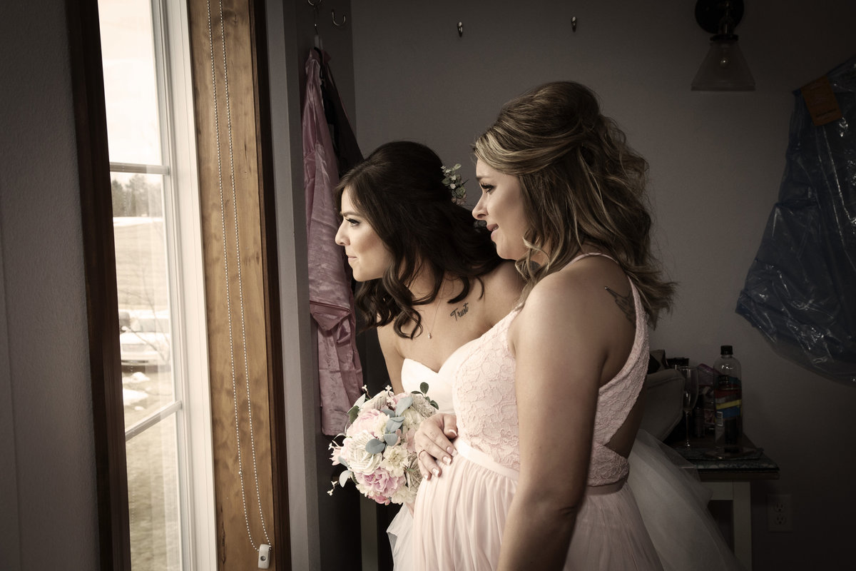 Sioux Falls wedding photography bride and maid of honor watching guests arrive at blue have barn South Dakota