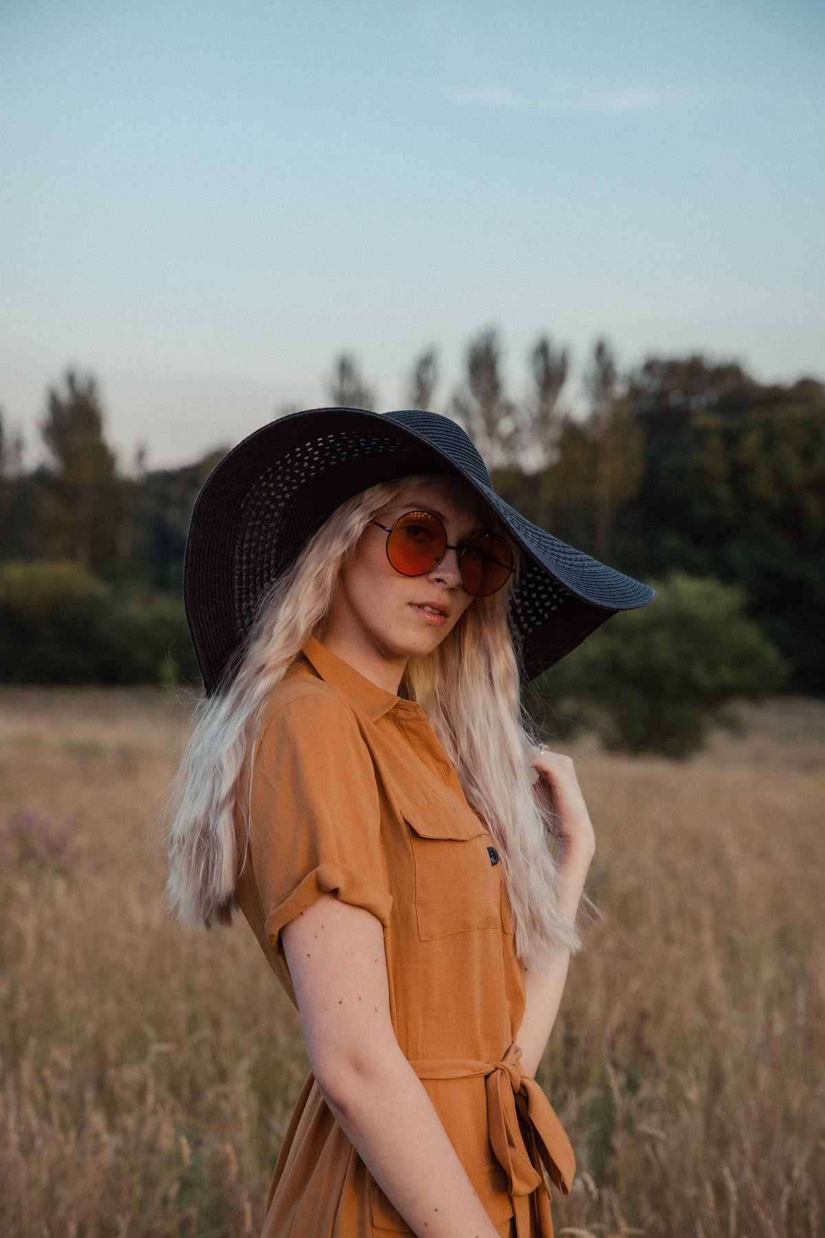 Amber stood  in the grass at golden hour, wearing orange sunglasses and a black straw hat