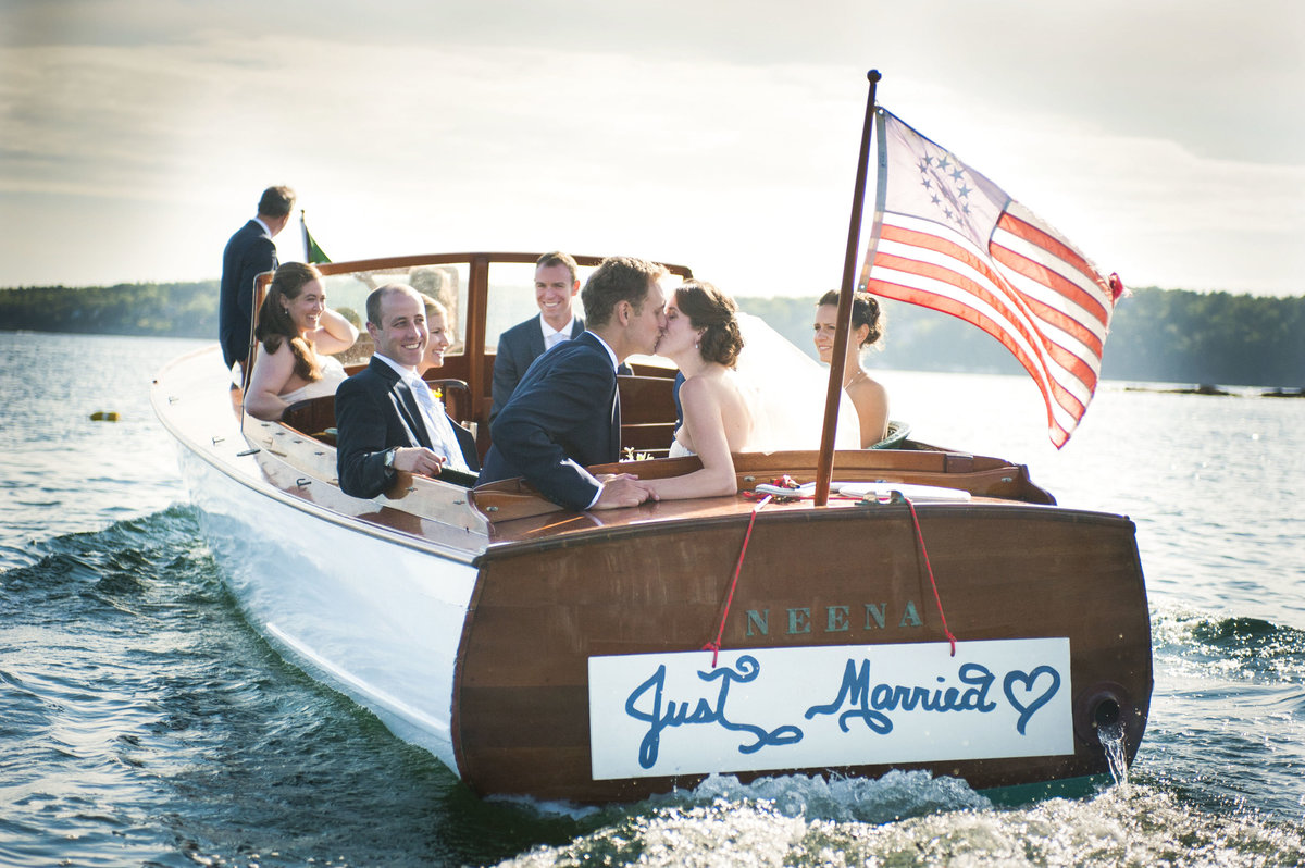 Bride & groom kiss in a boat filled with their bridal party leaving their wedding in South Bristol, Maine