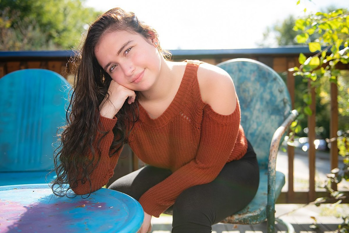 High school senior girl in rust-colored cold shoulder sweater leaning on blue table on deck at OhioPyle State Park in PA