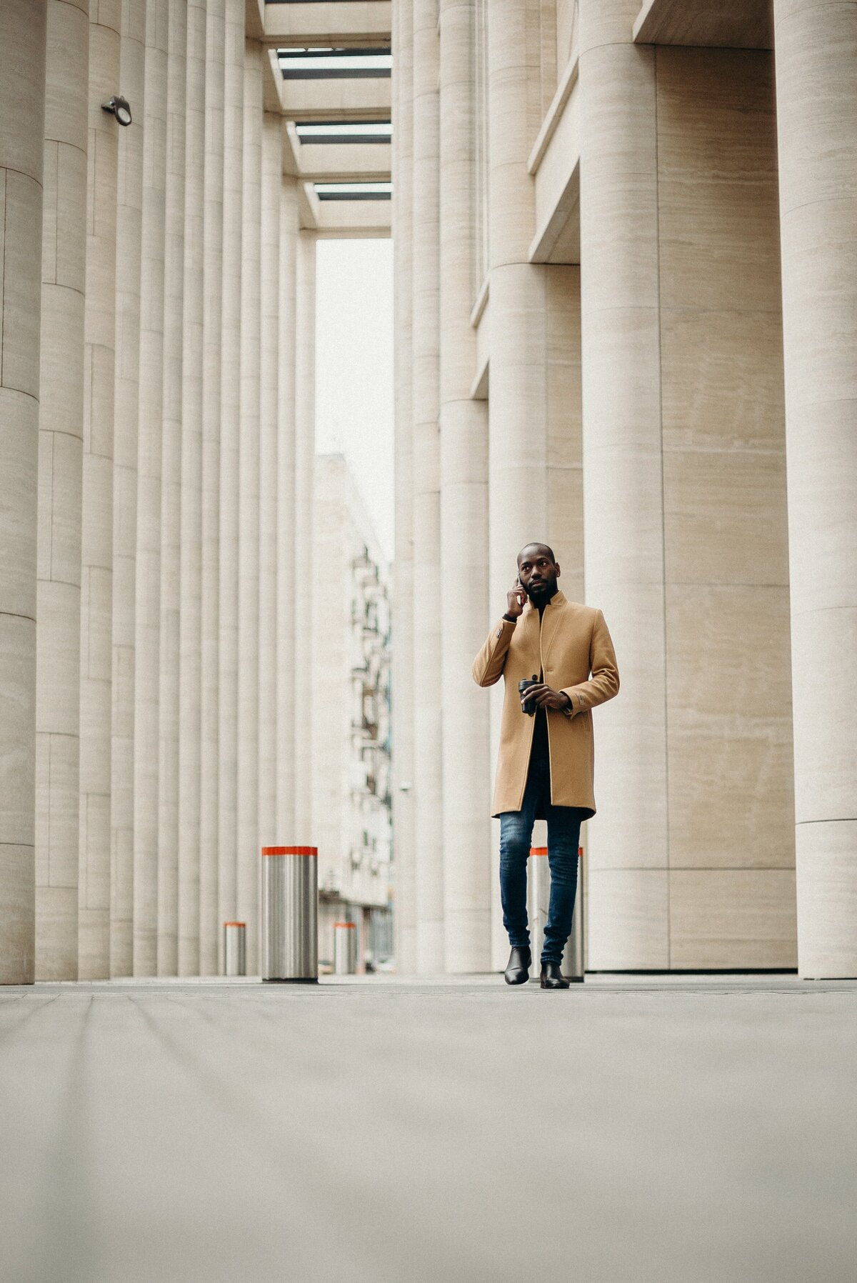 man-in-brown-coat-standing-beside-concrete-wall-3206149