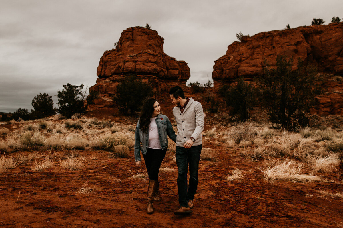 engaged couple walking in front of red rocks
