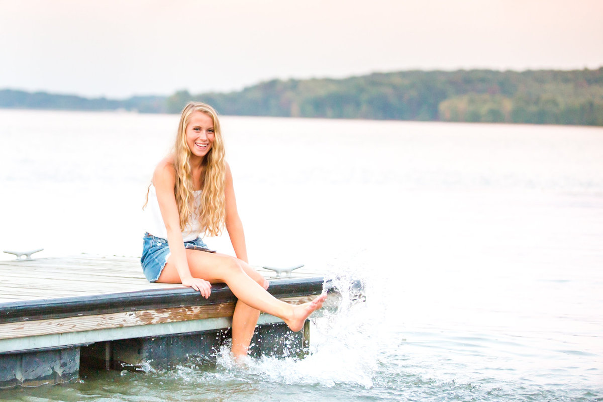 Teenage girl sits on the edge of a dock and kicks the water during high school senior portrait photography session