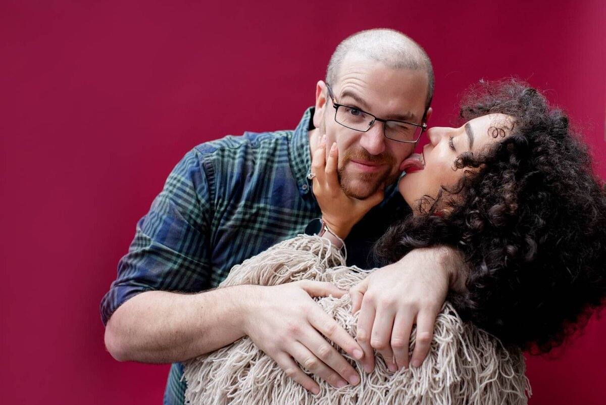 a fun woman with curly hair wearing a shaggy sweater licks her fiance's face
