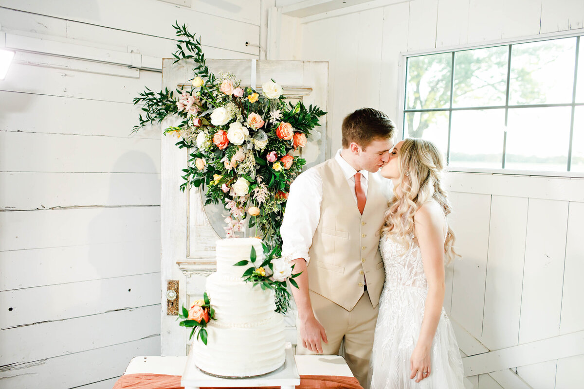 A bride and groom kissing each other by their wedding cake. Behind them is a gorgeous floral arrangement and an all white wedding cake with florals on it