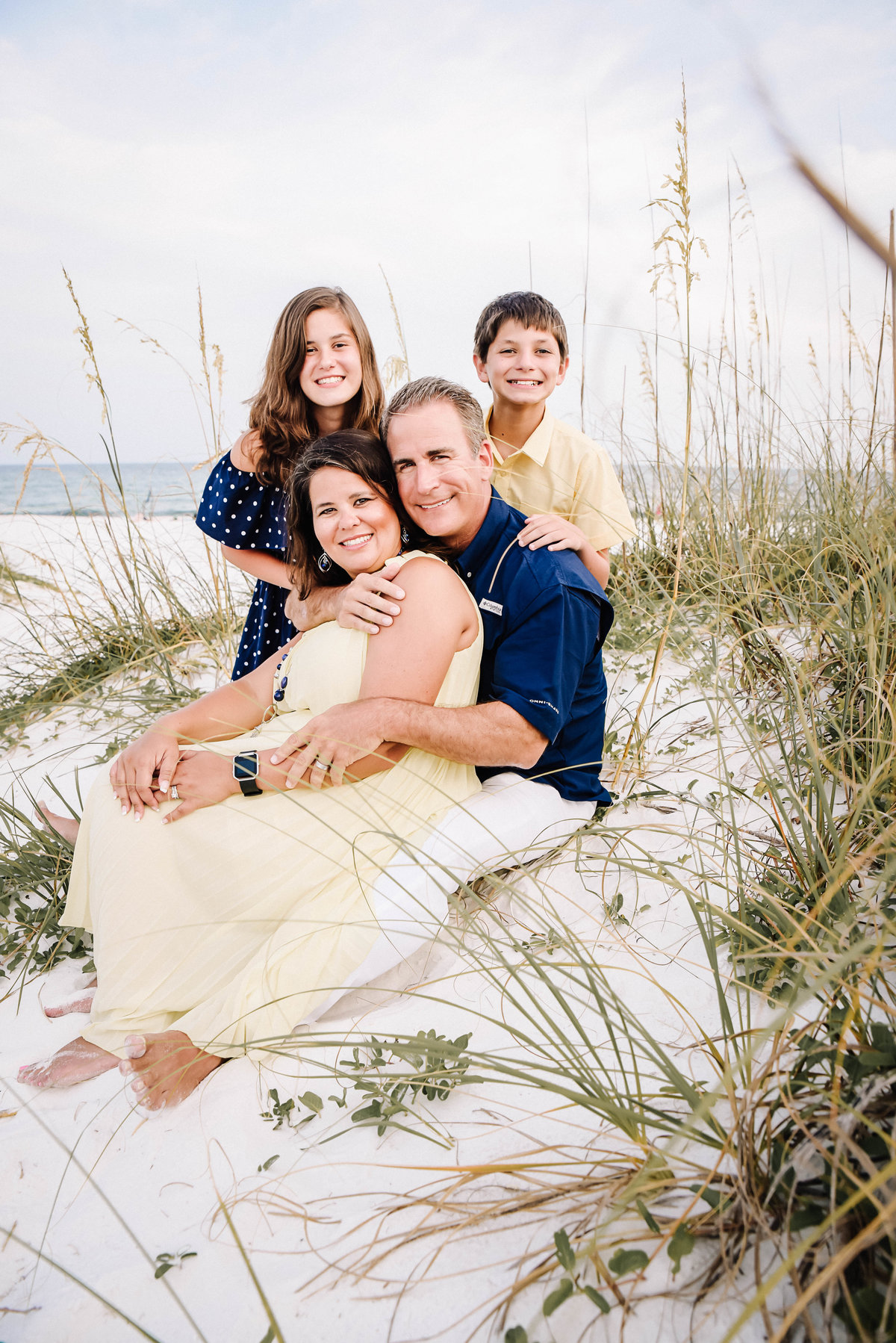 family sitting on the beach in Fort Walton Beach, FL