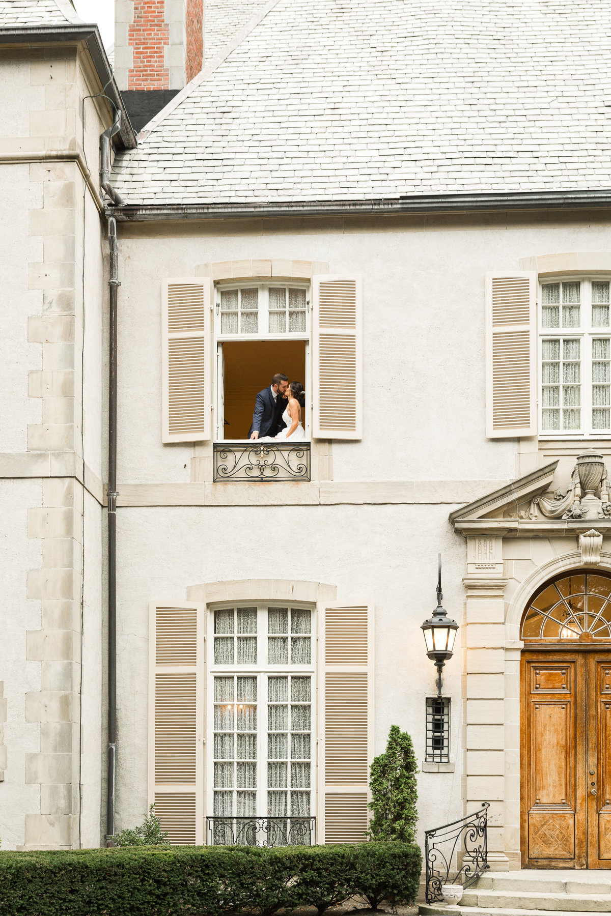 Bride and groom share a kiss on the balcony at the French chateau Glen Manor House