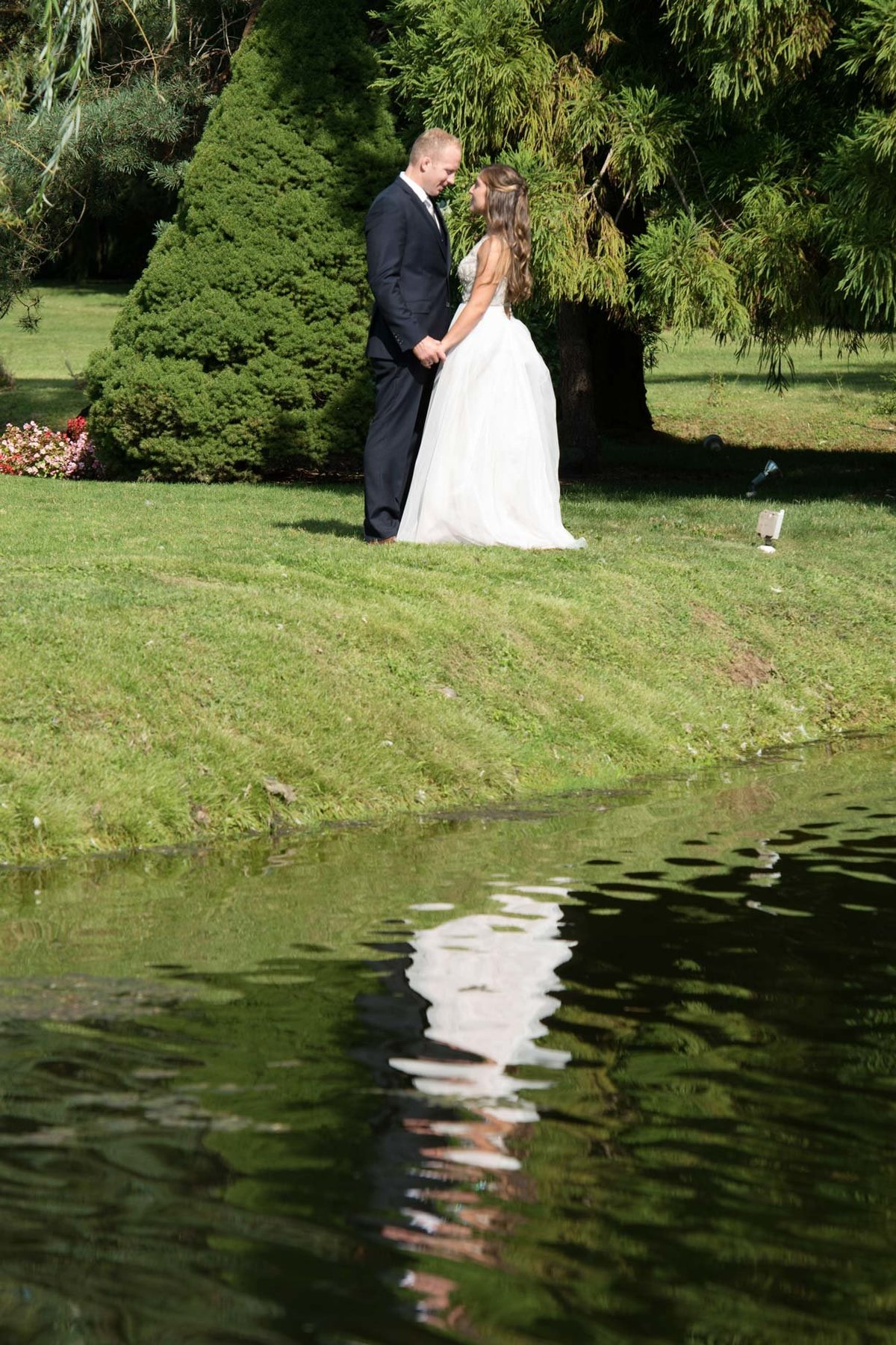 Bride and groom looking at one another right by the water at Flowerfield