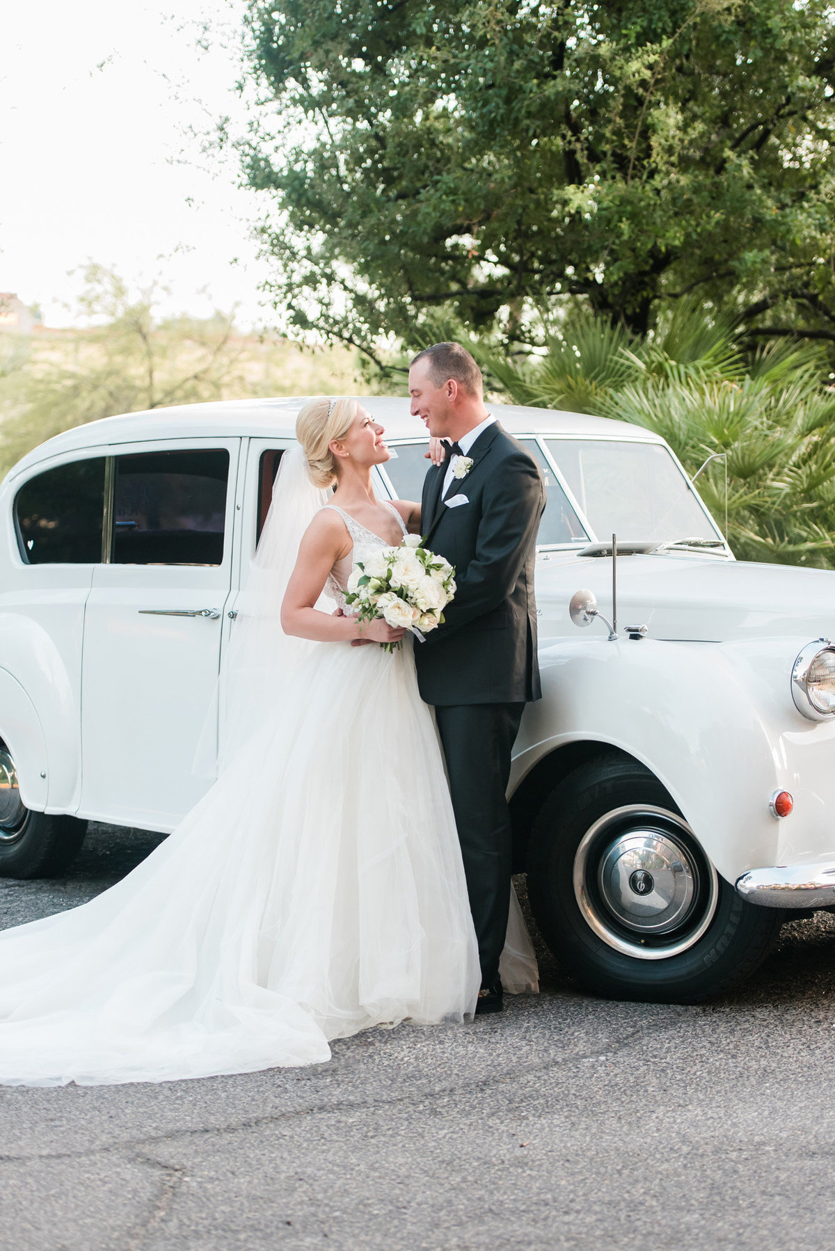 a bride and groom standing in front of a white vintage car at their wedding at JW Marriott Resort and Spa Las Vegas