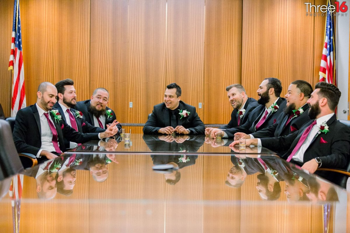 Groom and Groomsmen pose together having a board meeting
