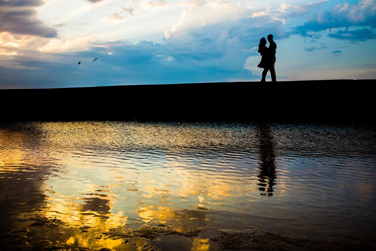 A couple hugs at sunrise during a North Avenue Beach engagement session.