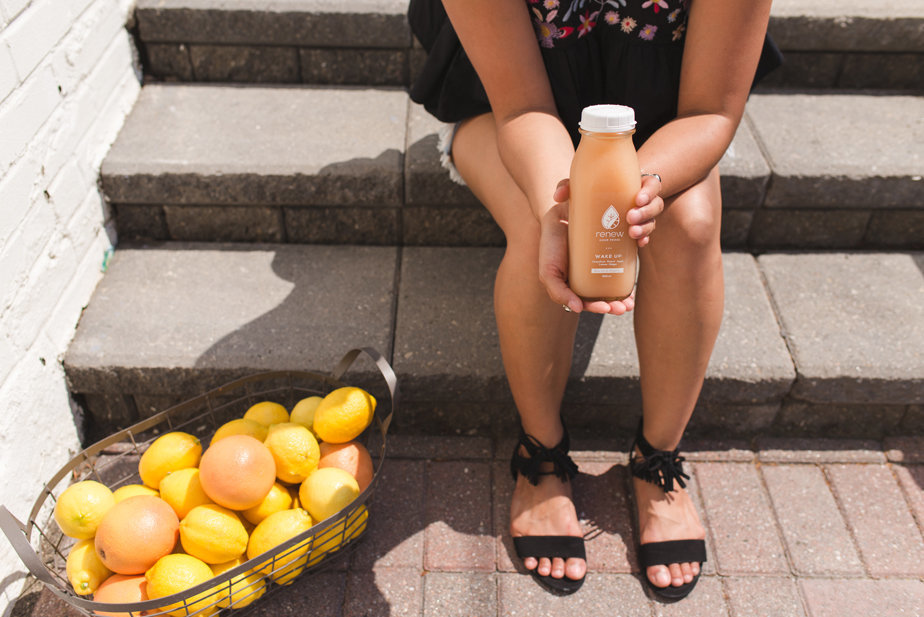 girl holding a bottle of juice with basket of oranges and grapefruit next to her