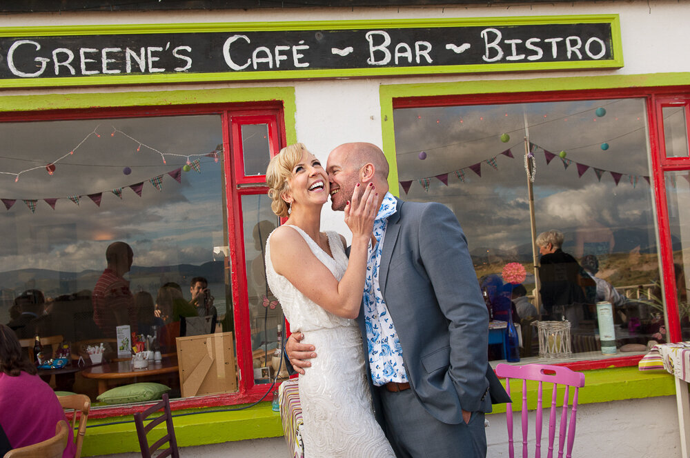 bride in v-neck column dress being kissed by groom in light grey wedding suit and floral shirt outside cafe at Inch Beach