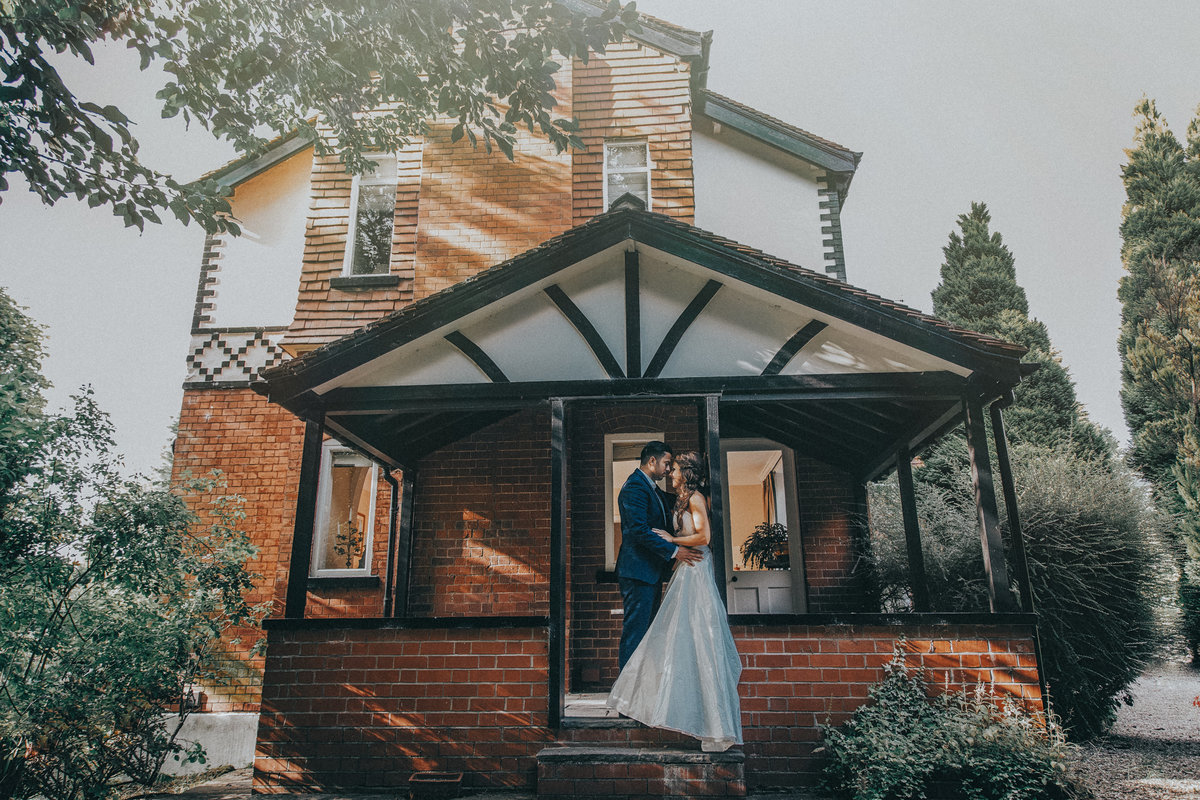 Bride & Groom kissing on porch f their home - Manchester Wedding Photographer Jono Symonds