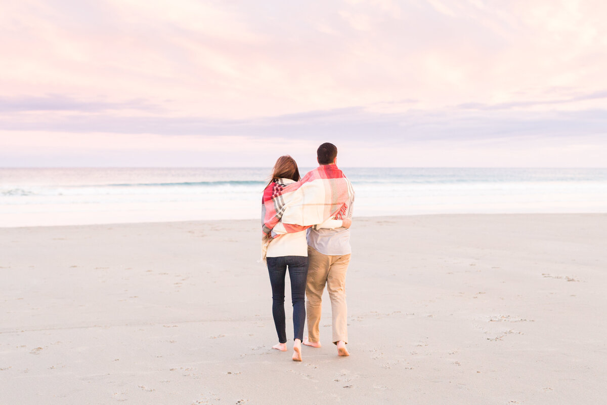 couple walking towards ocean during engagement session