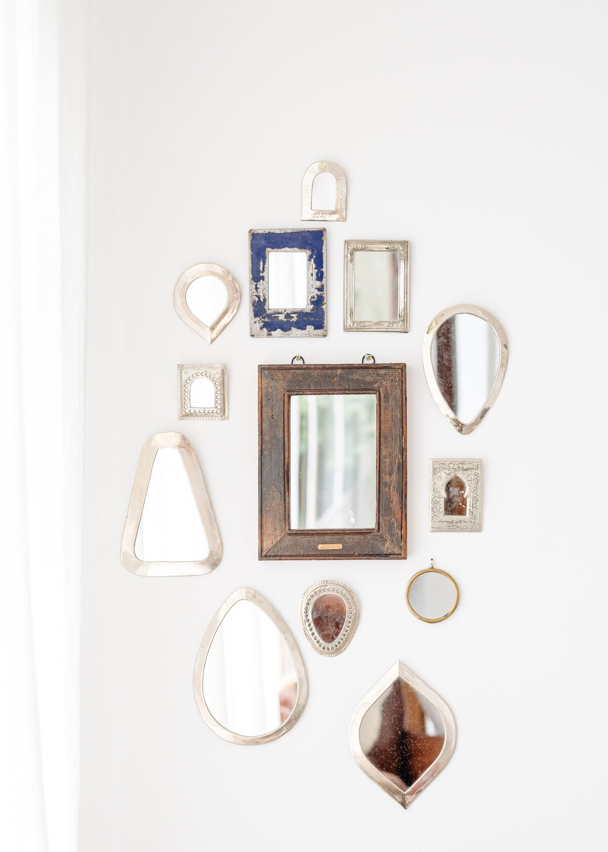 A selection of bohemian mirrors hang on a white wall as interior decor.