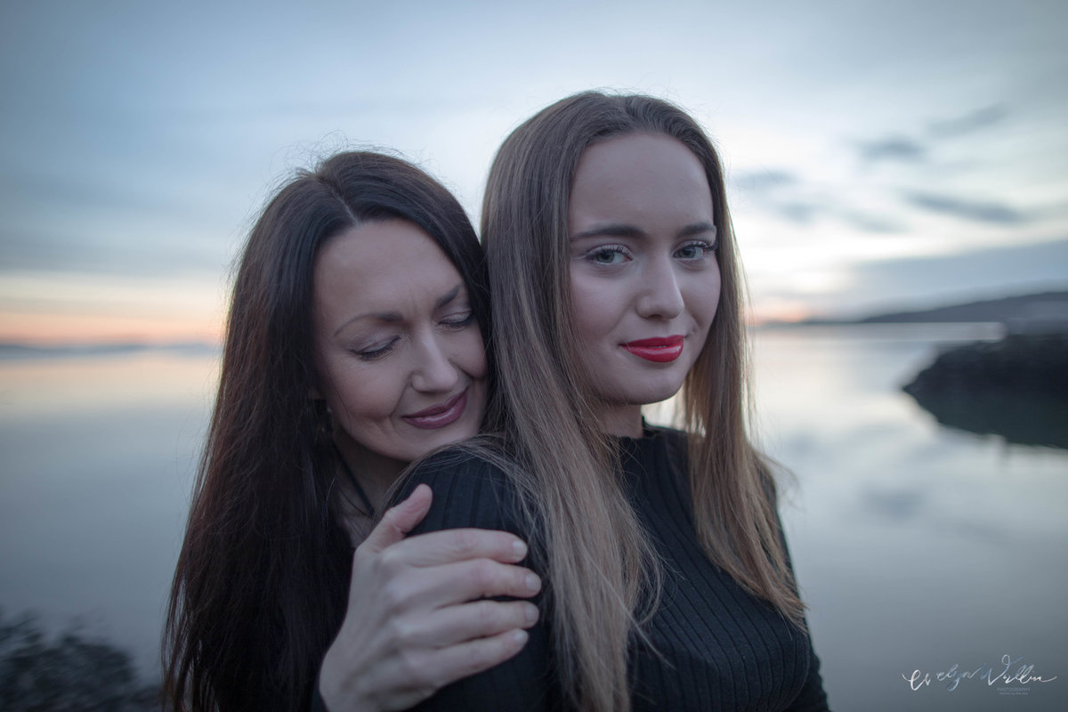 Mother holding her teenage daughter, closing her eyes, with the sea in the background