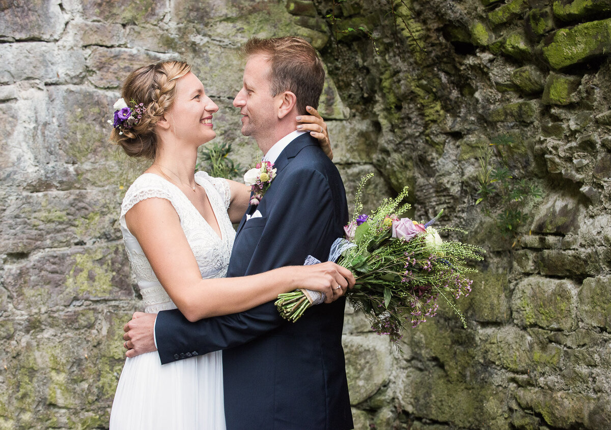 bride wearing a column style wedding dress with beaded top, holding a wild flower bouquet while embracing her groom, wearing a navy wedding suit while standing in a castle ruin