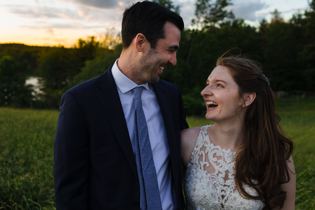 Kitz Farm Wedding couple laugh in the meadow as the sun sets behind them in Strafford NH