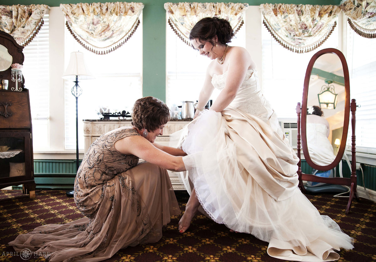 Mother of the bride helps with garter in the bridal suite at the Manor House in Littleton CO