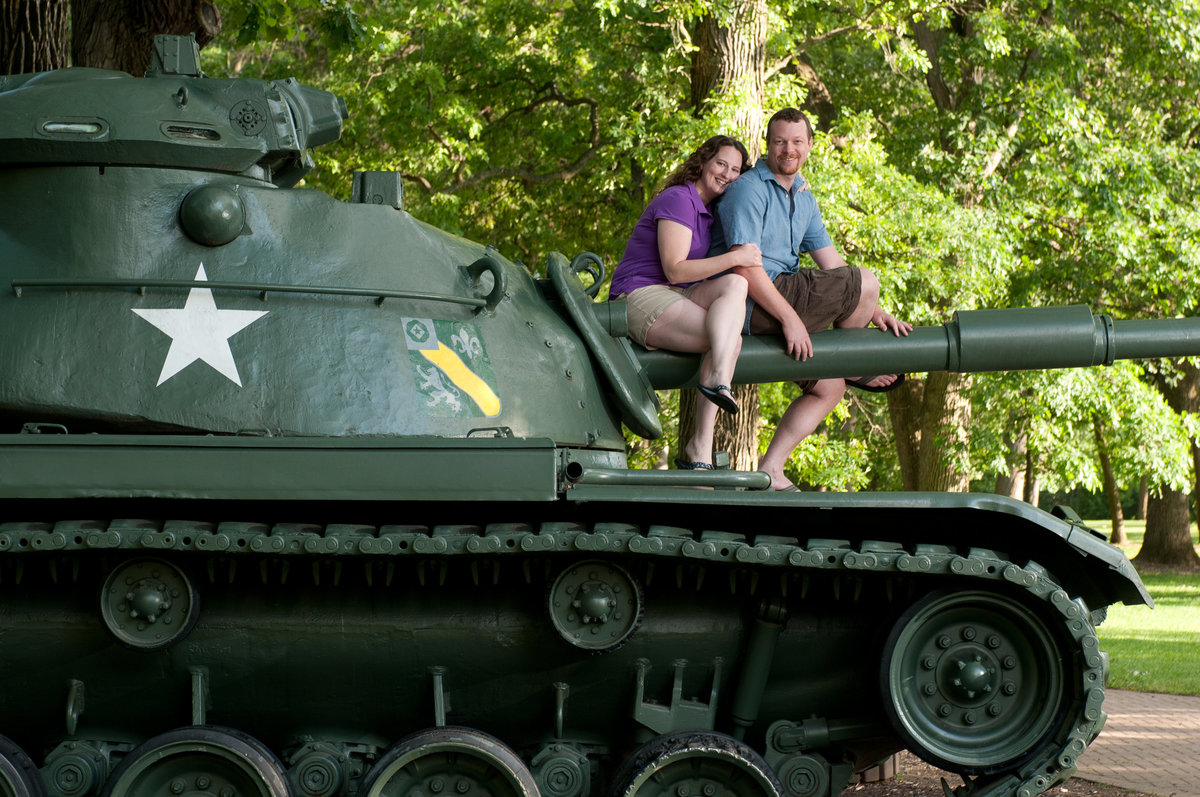 An engagement couple pose atop a tank at cantigny park